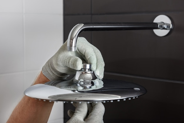 As mãos do trabalhador instalam a cabeça da torneira do chuveiro embutida.