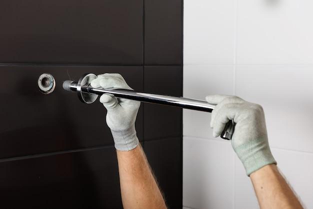 As mãos do trabalhador instalam o tubo da torneira do chuveiro embutido