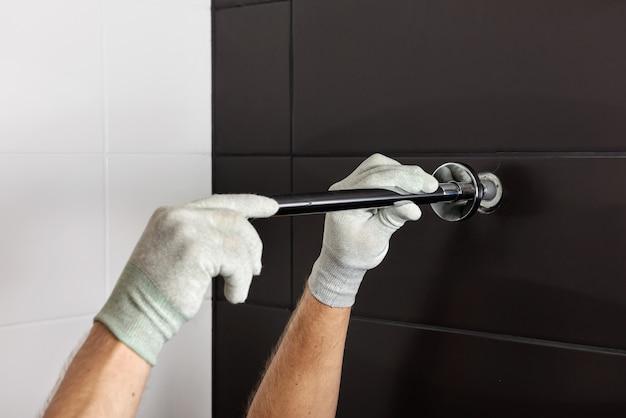 As mãos do trabalhador instalam o tubo da torneira do chuveiro embutido.