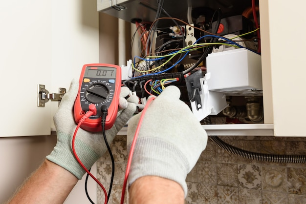 As mãos do trabalhador verificam a operacionalidade da eletrônica da caldeira a gás
