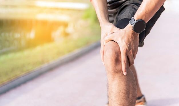 As mãos do uso do homem prendem em seu joelho ao correr na estrada no parque.