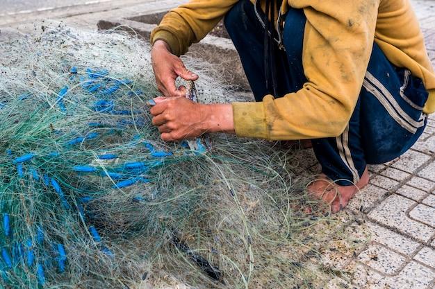 As mãos do velho pescador desembaraçam redes de pesca, nha trang