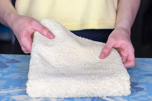 As mãos dobram uma toalha acariciada.