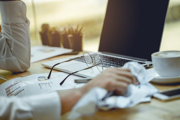 As mãos dos empresários estão amassando relatórios em papel.