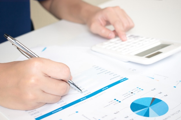 As mãos dos empresários estão calculando os dados de custo no gráfico para gerar renda no trabalho.