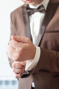 As mãos dos homens ajustam as abotoaduras nas mangas.