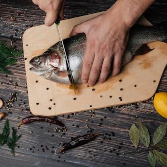 As mãos dos homens cortam peixe vermelho do conselho