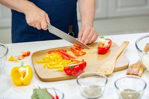 As mãos dos homens cortam pimenta vermelha e amarela na placa de madeira