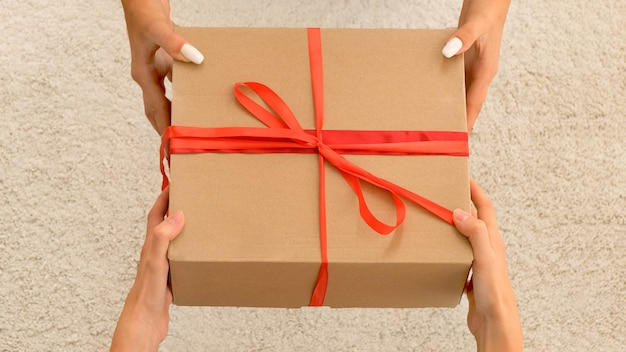 As mãos dos homens dão uma caixa com um presente para uma mulher