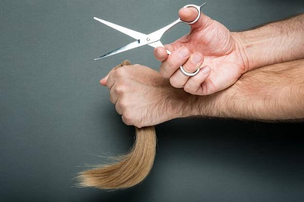 As mãos dos homens demonstram tesoura e cabelo cortado