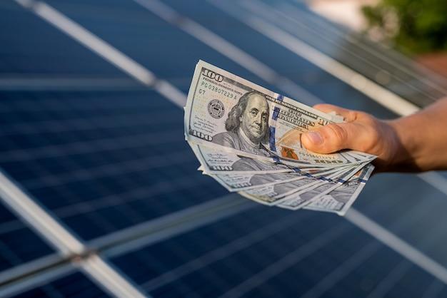 As mãos dos homens detêm dólares como lucro da produção de energia alternativa. painéis solares