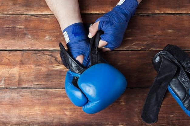 As mãos dos homens em bandagens de boxe e luvas de boxe em uma superfície de madeira. preparação do conceito para treinamento ou combate de boxe. vista plana, vista superior