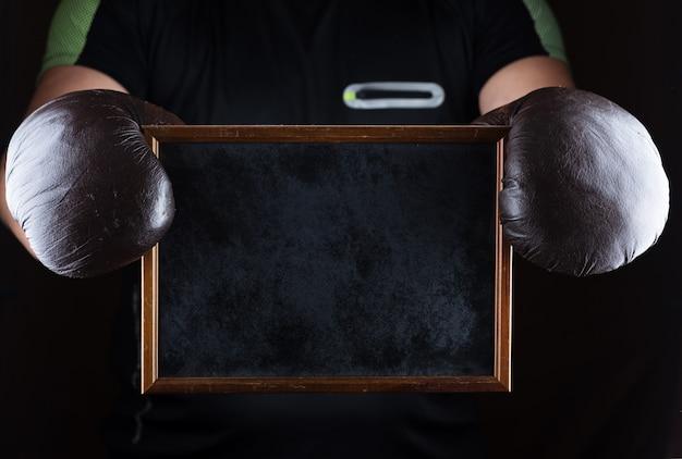 As mãos dos homens em luvas de boxe segurar um quadro negro vazio