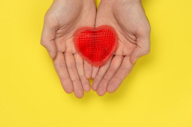 As mãos dos homens estão segurando um coração vermelho em uma parede amarela. amor, conceito de relacionamento.