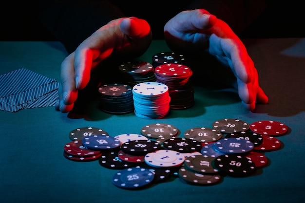 As mãos dos homens fazem uma aposta com fichas de jogo