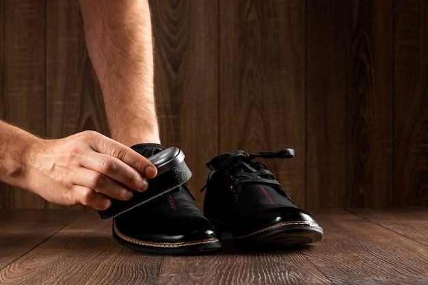 As mãos dos homens limpam sapatos pretos em uma parede de madeira. o conceito de engraxate, cuidados com a roupa, serviços.