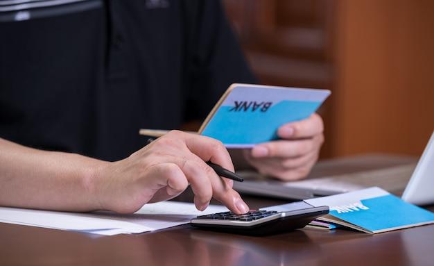 As mãos dos homens que seguram uma caderneta de banco e elaboram um orçamento.