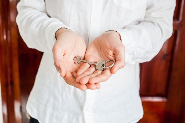 As mãos dos homens seguram a chave da casa em um fundo de porta de madeira. possuir o conceito imobiliário
