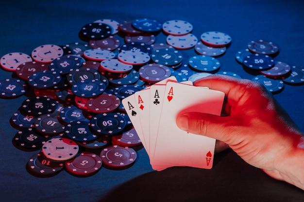 As mãos dos homens seguram cartas no fundo de jogar fichas de pôquer