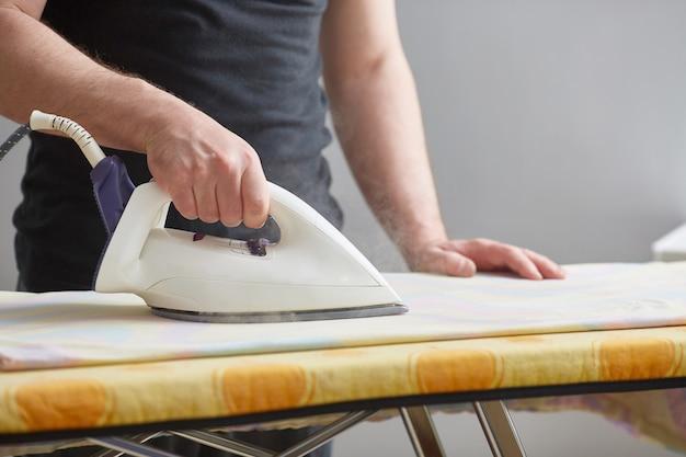 As mãos dos homens seguram ferro e ferro branco na tábua de passar. fechar-se. sem rosto. copie o espaço. os deveres domésticos são realizados por homens.