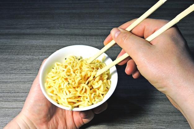 As mãos dos homens seguram macarrão com pauzinhos. macarrão chinês, paus, mãos.