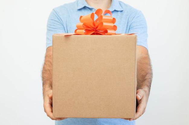 As mãos dos homens seguram uma caixa com uma fita vermelha em um fundo branco.