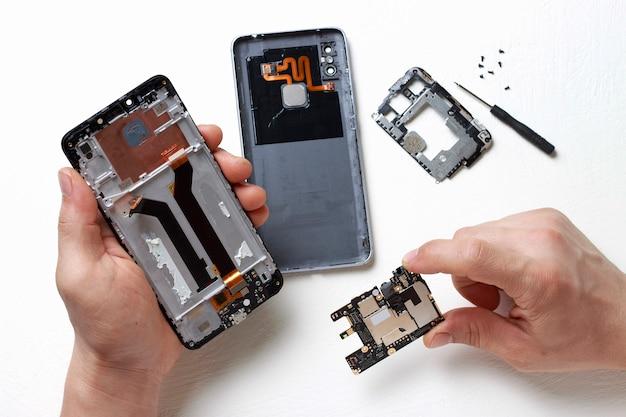 As mãos dos homens seguram uma chave de fenda nas mãos e reparam o smartphone quebrado