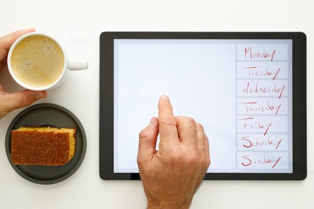 As mãos dos homens seguram uma xícara de café e usam um tablet eletrônico com os dias da semana