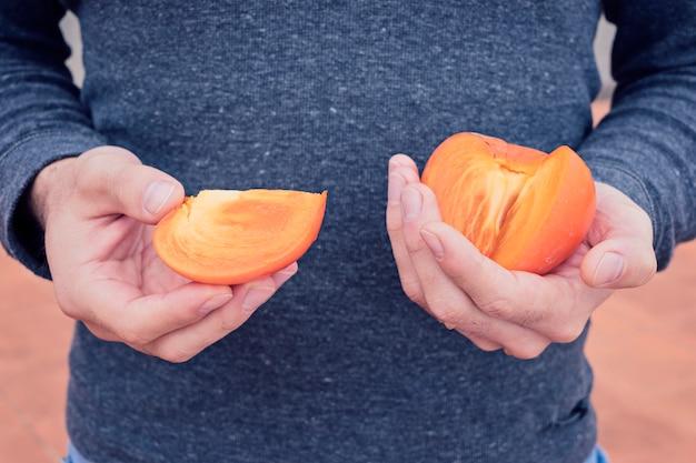 As mãos dos homens segurar um caqui maduro suculento
