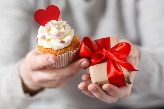 As mãos dos homens segurar um presente com uma fita vermelha e cupcake decorado com corações. dia dos namorados