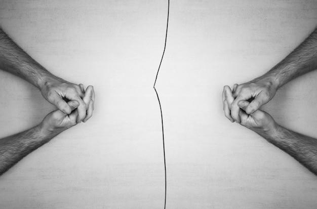 As mãos dos homens sentadas em frente uma da outra e uma rachadura no meio.