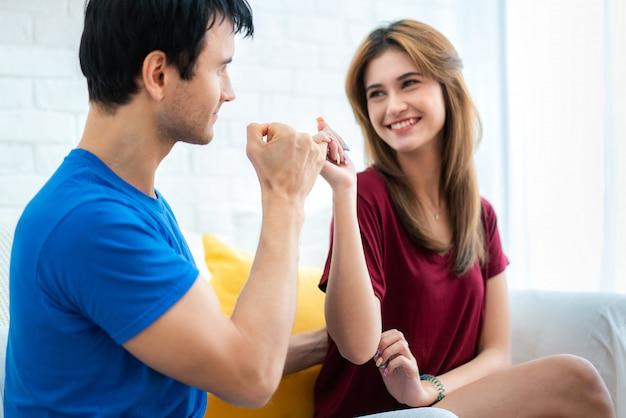 As mãos dos pares mostram pouco dedo no sofá na casa. amor romântico. mão para mindinho juro, mindinho prometer sinais de mão.