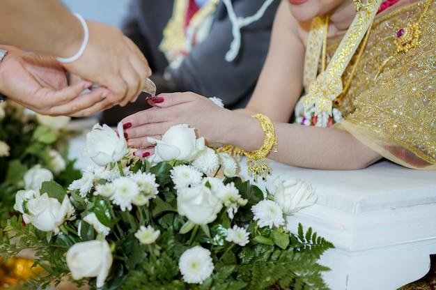 As mãos dos participantes molhando a concha na cerimônia de casamento.