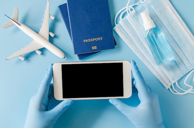 As mãos em luvas descartáveis seguram o smartphone e simulam modelo de avião, passaporte, máscara facial e spray desinfetante para as mãos