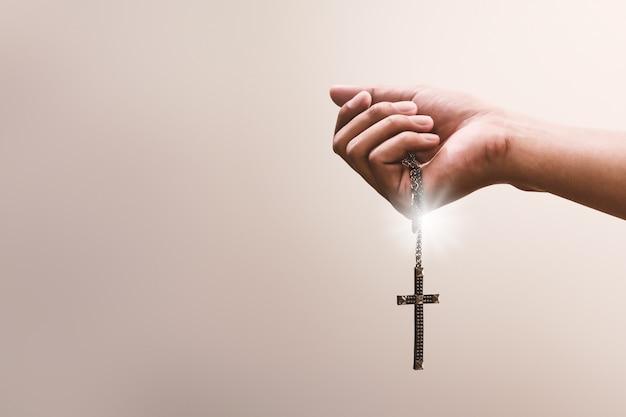 As mãos em oração seguram um crucifixo ou uma cruz de colar de metal com fé na religião e crença em deus. poder da esperança e devoção.