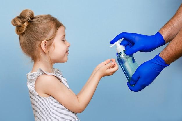 As mãos enluvadas despejam sabão líquido nas mãos da criança.