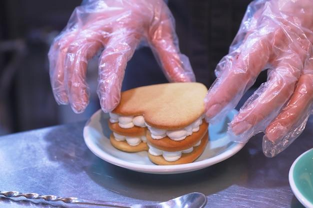 As mãos enluvadas do chef preparam um bolo de creme sobre uma mesa brilhante em um prato na cozinha
