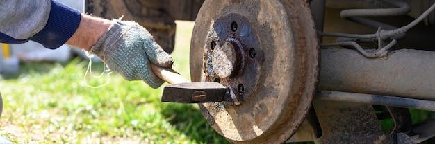 As mãos enluvadas dos homens consertam o próprio freio a tambor desmonta um disco preso com um martelo. reparo de freio de tambor de carro quebrado desmontado ao ar livre. bandeira