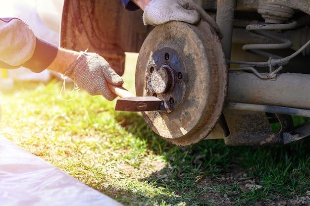 As mãos enluvadas dos homens consertam o próprio freio a tambor desmonta um disco preso com um martelo. reparo de freio de tambor de carro quebrado desmontado ao ar livre. chama