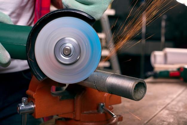 As mãos enluvadas seguram uma rebarbadora e cortam o tubo, muitas faíscas voam para os lados