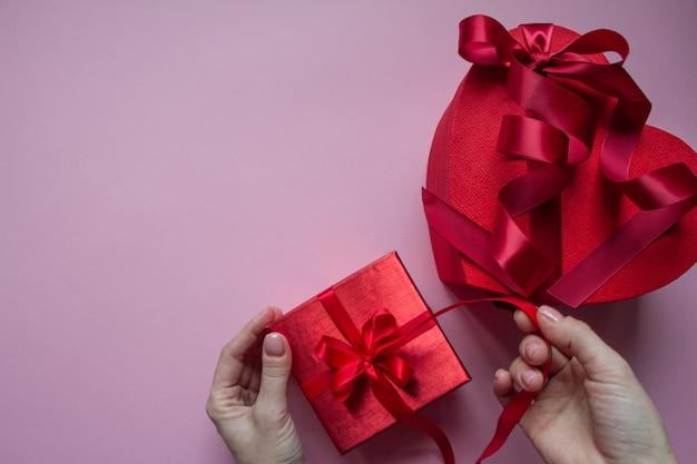 As mãos envolvem a forma de coração de caixa de presente vermelha com fita vermelha