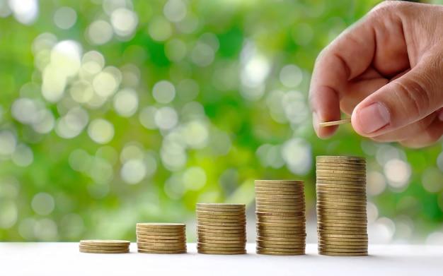 As mãos estão colocando moedas sobrepostas sobre uma natureza verde.