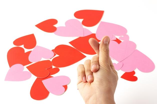 As mãos estão fazendo um símbolo de coração sobre corações vermelhos e rosa espalhados.
