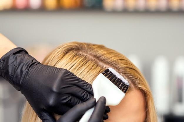 As mãos estão pintando o cabelo feminino em uma cor branca close-up.