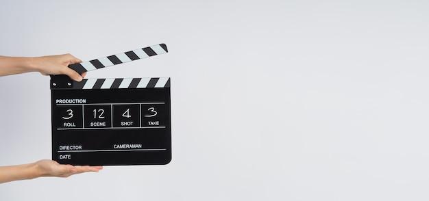 As mãos estão segurando claquete preta ou filme slate escrever em número. ele usa na produção de vídeo, filme, cinema, indústria cinematográfica em fundo branco.
