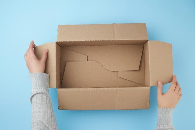 As mãos estão segurando uma caixa aberta vazia de papelão marrom