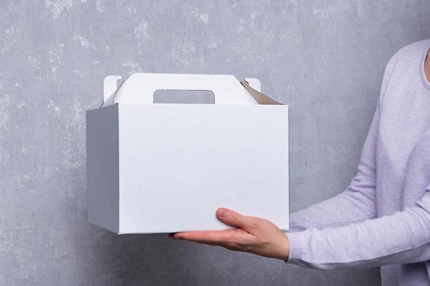 As mãos estão segurando uma caixa de papelão branca. embalagens para bolos e pastéis.