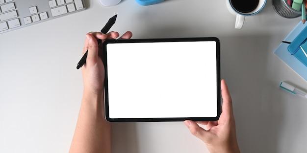 As mãos estão usando um tablet de computador de tela branca em branco e uma caneta stylus em uma mesa de trabalho branca
