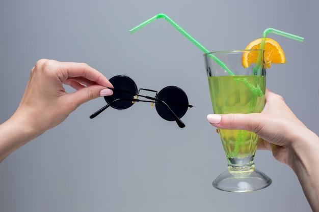 As mãos femininas com coquetel e óculos de sol no espaço cinza