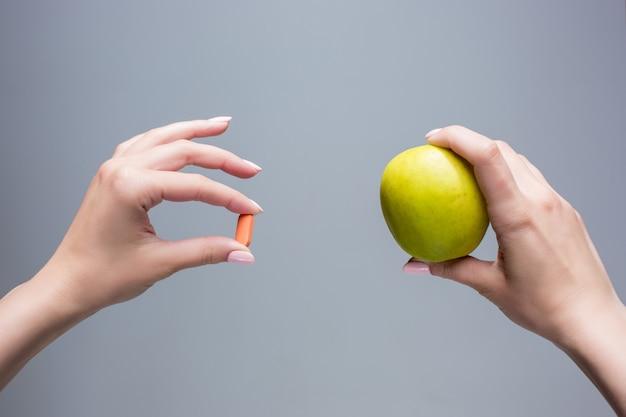 As mãos femininas com maçã e comprimidos em fundo cinza